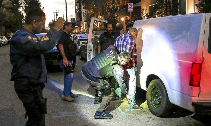 An suspected criminal alien is detained by Immigration and Customs Enforcement (ICE) agents in Los Angeles, Oct. 14, 2015. The number of ICE detentions and deportations from California has dropped since the state passed the Trust Act in October 2013, which set limits on California law enforcement cooperation with federal immigration authorities. (John Moore/Getty Images)