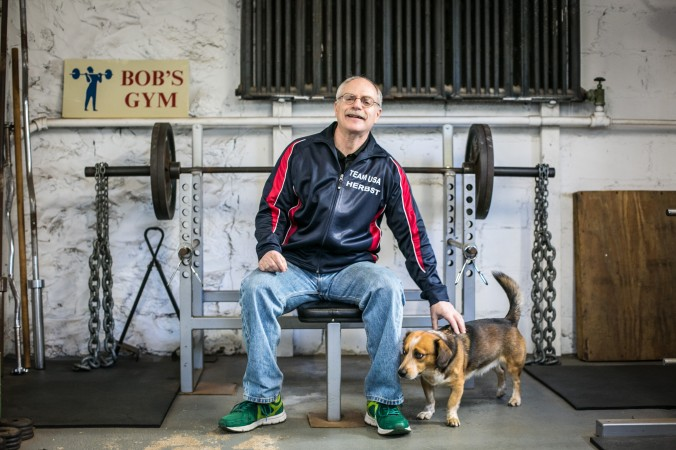 Robert Herbst with his dog Denny, at the gym inside his home in Larchmont, N.Y., on Feb. 24, 2017. (Benjamin Chasteen/Epoch Times)