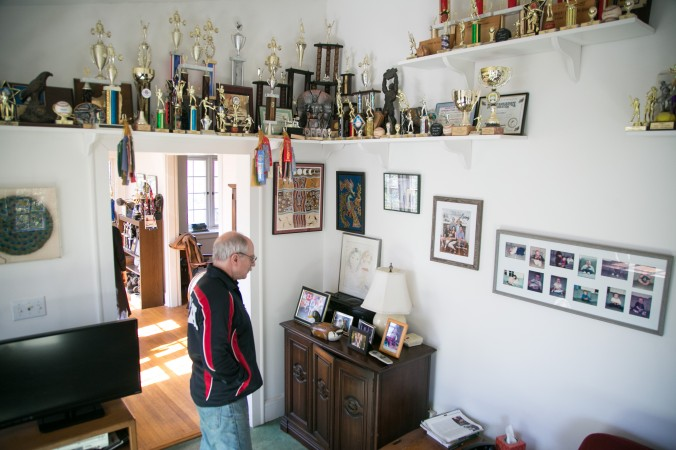 Robert Herbst with the metals and trophies he has won  throughout the years along with his children trophies they have won playing various sports. (Benjamin Chasteen/Epoch Times)