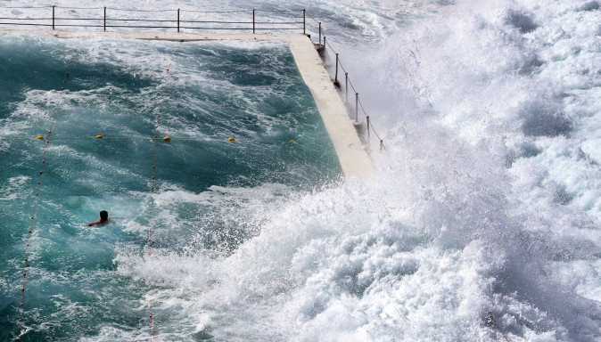 A swimmer at Bondi's ocean pool watches as a big wave pours into the pool at Bondi Beach in Sydney on March 6, 2017. (William West/AFP/Getty Images)