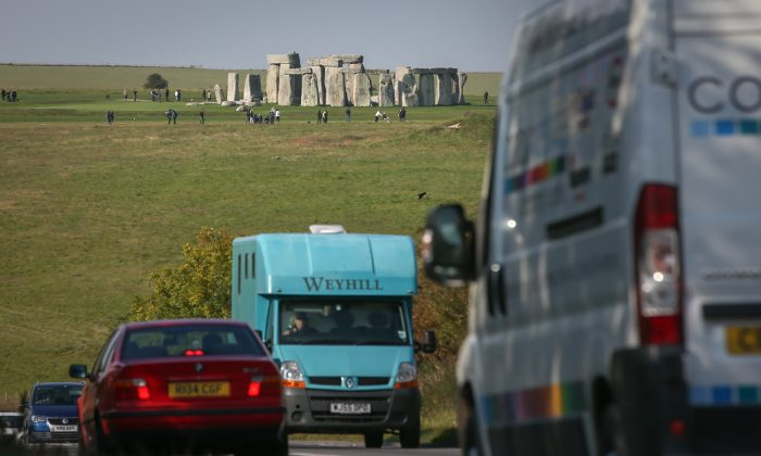 Traffic passes along the busy A303 that runs besides the ancient neolithic monument of Stonehenge in Wiltshire, England, on Oct. 13, 2015. The U.K. Government is planning to build a $2.4 billion tunnel under the UNESCO-listed ancient monument, but opponents say it risks unsettling ancient burial sites.(Matt Cardy/Getty Images)