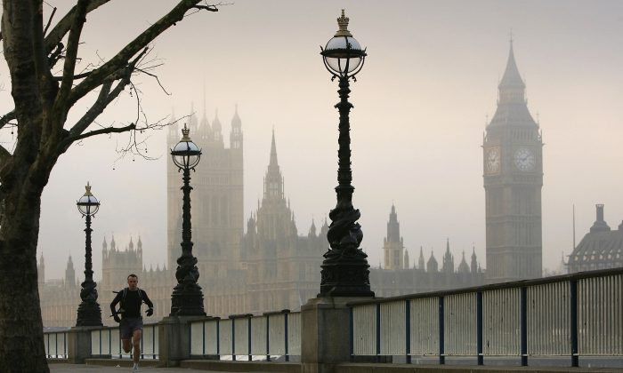 A man jogs down the South Bank as fog covers London's Houses of Parliament on Dec. 20, 2006. (Scott Barbour/Getty Images)