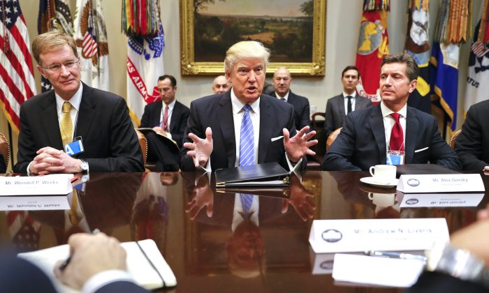 President Donald Trump speaks while hosting a breakfast with business leaders in the Roosevelt Room of the White House in Washington,  Jan. 23, 2017. At left is Wendell P. Weeks, Chief Executive Officer of Corning, at right is Alex Gorsky Chairman and Chief Executive Officer of Johnson & Johnson. (AP Photo/Pablo Martinez Monsivais)
