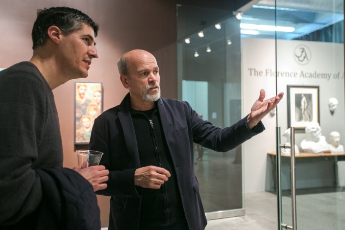 Founder of The Florence Academy of Art Daniel Graves (R) talks about a painting with artist Edward Minoff at the opening of the Consecrated Reality art exhibit, in the gallery of The Florence Academy of Art-U.S. branch, on May 1, 2016. (Milene Fernandez/Epoch Times)