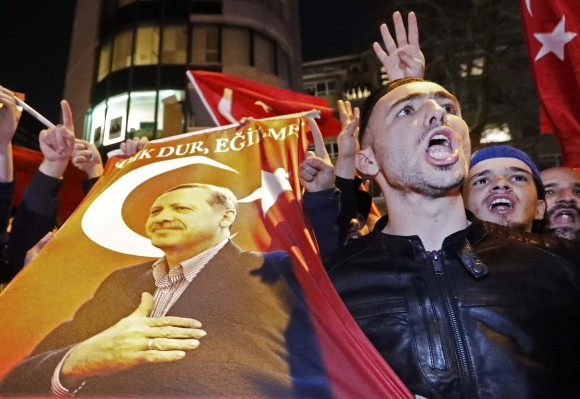 Demonstrators with banners of Turkish President Recep Tayyip Erdogan gather outsidethe Turkish consulate to welcome the Turkish Family Minister Fatma Betul Sayan Kaya, who decided to travel to Rotterdam by land after Turkish Foreign Minister Mevlut Cavusoglu's flight was barred from landing by the Dutch government, in Rotterdam, Netherlands March 11, 2017.  (REUTERS/Yves Herman    TPX IMAGES OF THE DAY)