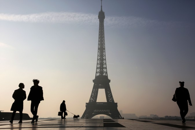 People walk on the Parvis des Droits de l'Homme square near the Eiffel tower in Paris on March 13, 2017. (Ludovic Marin/AFP/Getty Images)