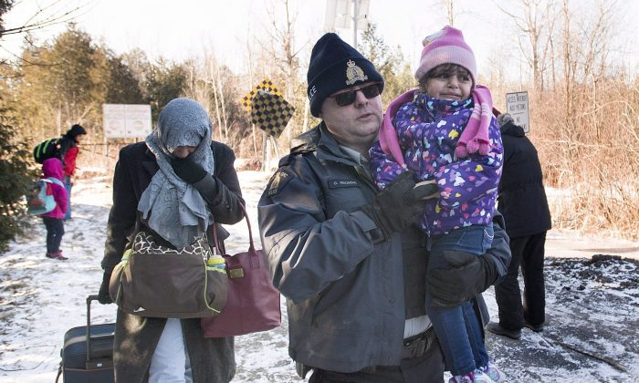 An RCMP officer escorts a woman and a child claiming to be from Yemen as they cross the U.S.-Canada border in Hemmingford, Que., on March 5, 2017.  (The Canadian Press/Graham Hughes)
