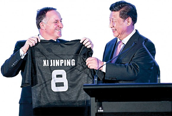 Former New Zealand Prime Minister John Key presents a rugby jersey to Chinese leader Xi Jinping in Wellington, New Zealand, on Nov. 20, 2014. China has become the biggest buyer of New Zealand farmlands, and Shanghai Pengxin is now New Zealand's third-largest dairy producer. (Hagen Hopkins/Getty Images)