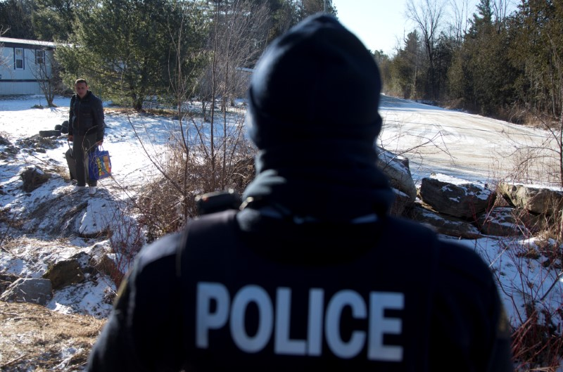 A man is confronted by a Royal Canadian Mounted Police officer as he prepares to cross the U.S.-Canada border leading into Hemmingford, Quebec.  (REUTERS/Christinne Muschi)