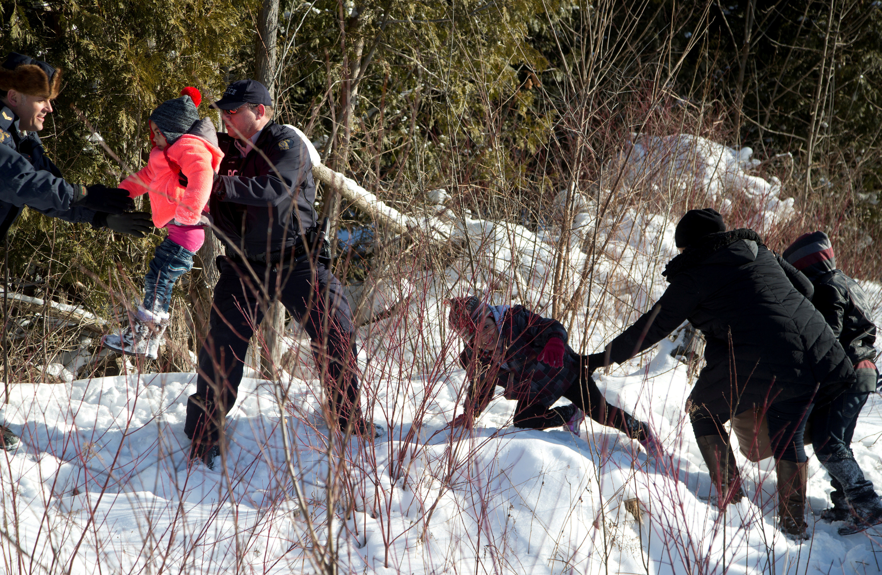 Royal Canadian Mounted Police (RCMP) officers assist a child from a family that claimed to be from Sudan as they walk across the U.S.-Canada border into Hemmingford, Canada, from Champlain in New York, U.S. on Feb. 17, 2017. (REUTERS/Christinne Muschi)