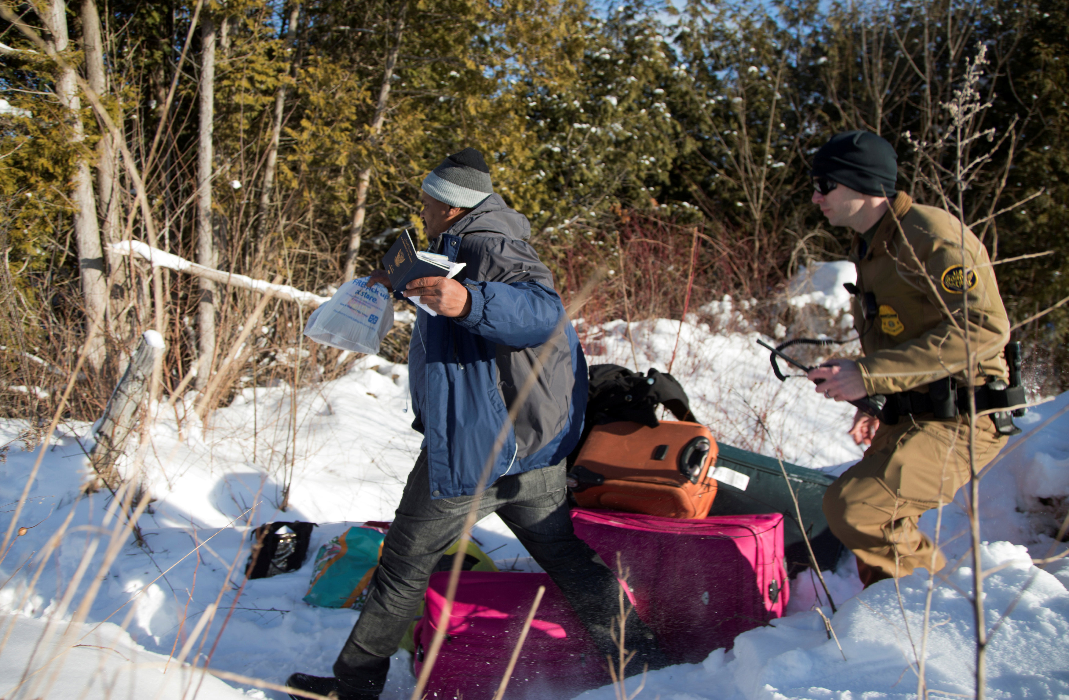 A man who claimed to be from Sudan runs for the border holding his family's passports as he is chased by a U.S. border patrol officer as he was detained after his family crossed the U.S.-Canada border into Hemmingford, Canada, from Champlain in New York, U.S. on Feb. 17, 2017.  (REUTERS/Christinne Muschi)