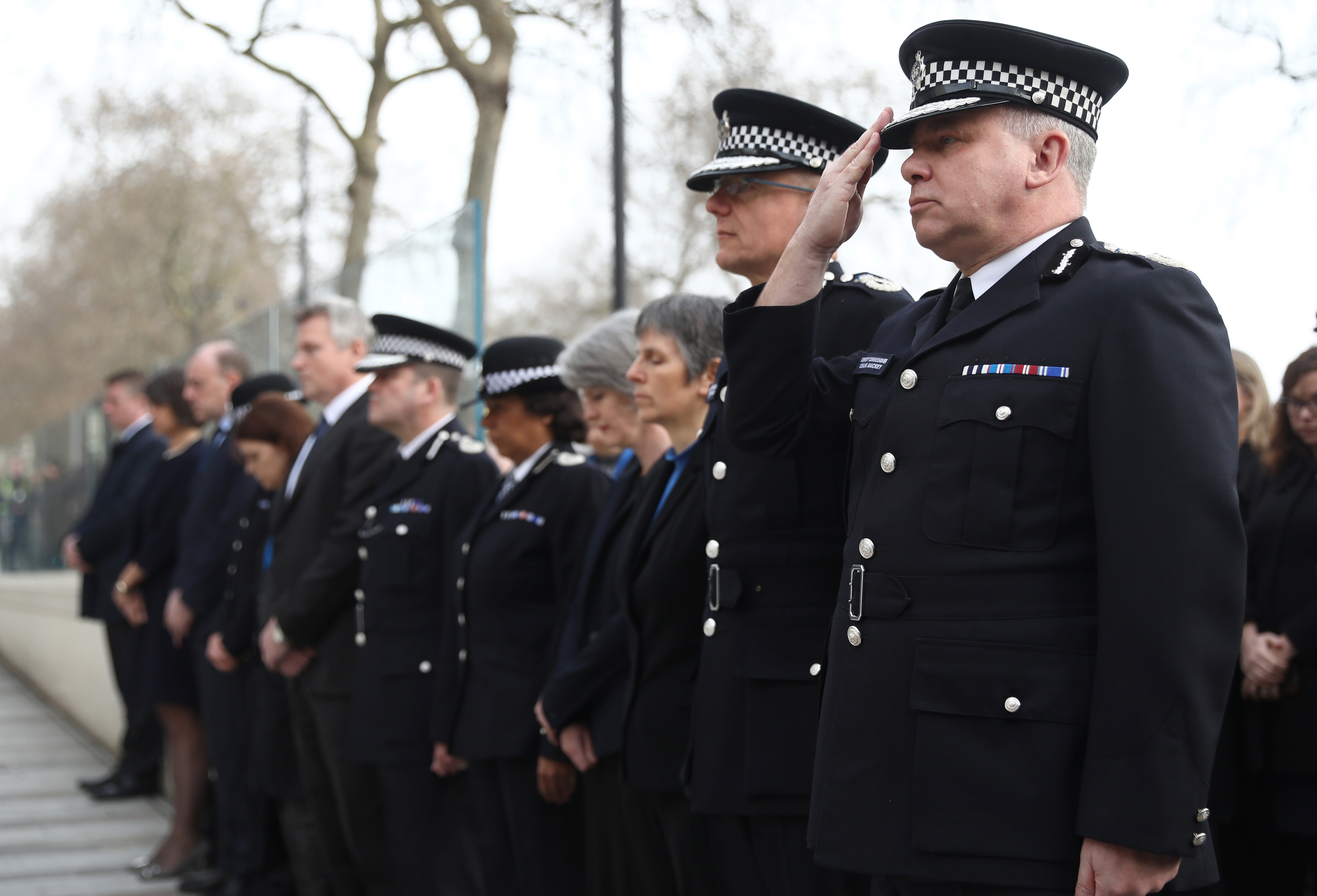 Police officers salute during a minute's silence outside New Scotland Yard. (REUTERS/Neil Hall)