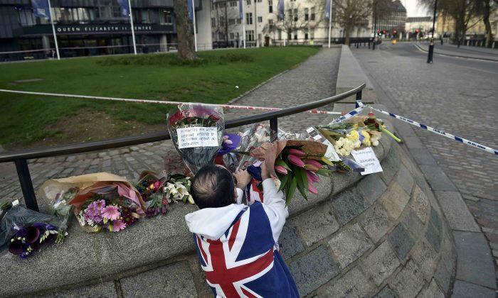 A man wears a Union Flag sweatshirt near the Houses of Parliament in Westminster the day after an attack, in London on March 23, 2017. (REUTERS/Hannah McKay)
