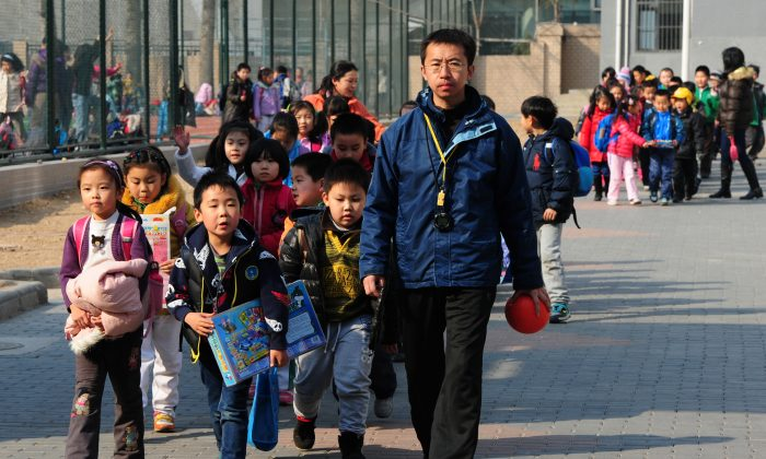 School children leave their elementary school in Beijing on March 13, 2012.  The plight of a Chinese father, posted online recently, resonated with an economically disenfranchised public.  (Mark Ralston/AFP/Getty Images)