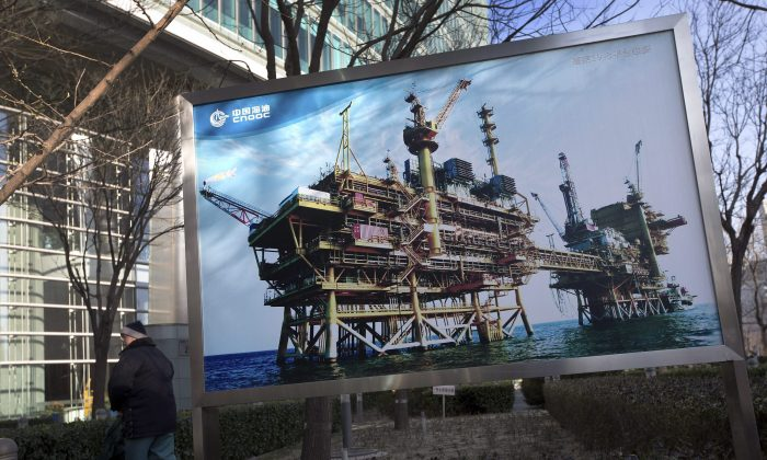 A photo of the state-owned China National Offshore Oil Corp. (CNOOC) platform outside its headquarters in Beijing, China. After Canada approved CNOOC's takeover of Canadian oil and gas producer Nexen, it vowed to reject any future foreign takeovers in the oil sands sector by state-owned companies. (AP Photo/Andy Wong)