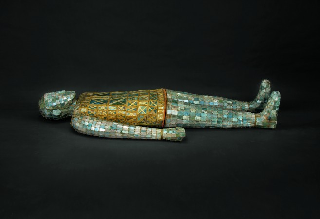 "Burial suit of Dou Wan, Western Han Dynasty (206 B.C.–A.D. 9). Jade (nephrite) with gold wire. Hebei Provincial Museum and Hebei Provincial Institute of Cultural Relics.  This jade suit was excavated from the tomb of Dou Wan, wife of Prince Liu Sheng of Zhongshan. Wan's body was encased and sealed in this suit. Its 2,400 rectangular plaques of jade are each meticulously shaped and fitted together with gold wire and silk ribbons. A Han Dynasty belief stipulated that if a deceased body was be encased in jade and its orifices plugged, preventing ""the essence of life"" from escaping, the person could attain immortality."