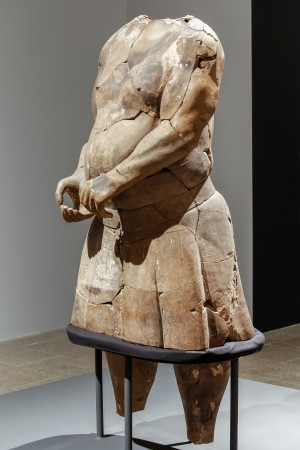 "Strongman, Qin Dynasty (221–206 B.C.). Earthenware, Emperor Qinshihuang's Mausoleum Site Museum (The Metropolitan Museum of Art). ""The unique feature of this sculpture is the depiction of human anatomy, which you don't find in Chinese art any time before the Qin Dynasty,"" said Zhixin Jason Sun, the curator of Chinese art at The Met. This large figure was found with ten others in a pit near the First Emperor's tomb. The group is believed to have represented an acrobatics troupe performing at the imperial court. Acrobatics in China originated in antiquity, and by the Qin–Han era had developed a full repertoire of moves, including rope walking and sword swallowing. The figure has an imposing physique and brawny hands, which together with his wide stance suggest his role as a strongman. He and a partner once held a pole, atop which another performer could swing, balance, and twist. The striking accuracy of his anatomy, hitherto unknown in Chinese figural art, has led to speculation that he was inspired by the Hellenistic sculptures that Alexander the Great introduced into Central Asia a century earlier."