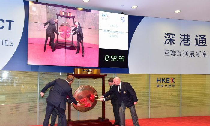 Banging the Gong to launch the GFI HKFC Rugby 10;s tournament and to open afternoon trading at the Hong Kong Stock Exchange on Wednesday March 29, 2017 are (L-R) special guest Josh Lewsey, Scott Tathem of title sponsors GFI Asia Pacific,  David Nazer Chairman of Organising Committee and Vern Reid Chairman of HKRU. (Bill Cox/Epoch Times)