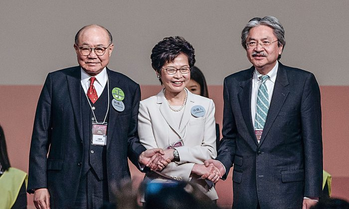 Carrie Lam (C), Hong Kong's chief executive-elect stands on stage with candidates for Hong Kong's chief executive John Tsang (R), Hong Kong's former financial secretary, and Woo Kwok-hing (L), retired judge, after the announcement of Hong Kong's chief executive election on March 26, 2017. (Anthony Kwan/Getty Images)