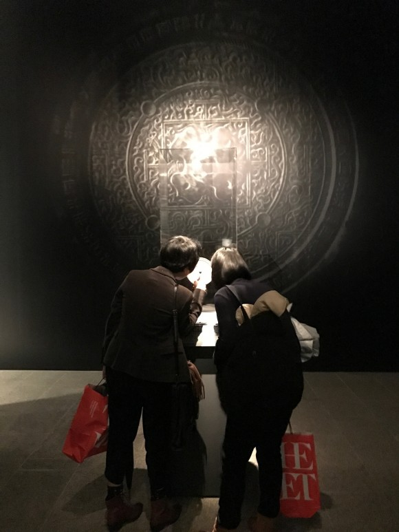 "Two women look at the Han Dynasty mirror on display at the ""Age of Empires"" exhibition at The Metropolitan Museum of Art. (Milene Fernandez/Epoch Times)"