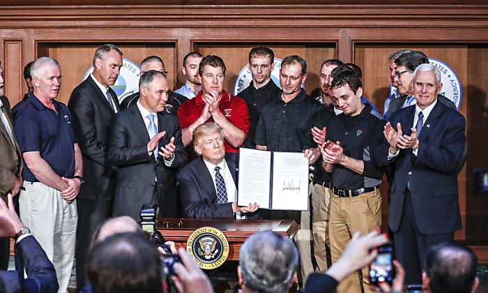 President Donald Trump, accompanied by Environmental Protection Agency Administrator Scott Pruitt (3rd L) and Vice President Mike Pence (R) is applauded as he hold up the signed Energy Independence Executive Order at EPA headquarters in Washington on March 28, 2017. (AP Photo/Pablo Martinez Monsivais)
