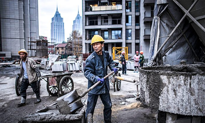 Construction workers at a residential skyscraper in Shanghai on Nov. 29, 2016. On-the-ground research in China shows that only state-owned enterprises are hiring, under the direction of the regime, while private enterprises  are not. (JOHANNES EISELE/AFP/Getty Images)