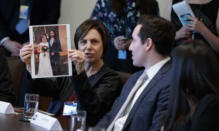 Pam Garozzo holds up a photograph of her late son Carlos during a listening session on opioid and drug abuse with President Donald Trump, Wednesday, March 29, 2017, in the Cabinet Room of the White House in Washington. (AP Photo/Evan Vucci)