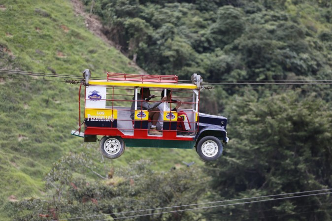 "Tourists ride a cable car in the form a of a Chiva, a bus used to serve rural routes, in Pitalito, Colombia, on April 5, 2017. The ride called ""La Chiva Voladora"" costs about $0.70 and runs about 800 meters (875 yards) from one side of a hill to another. (AP Photo/Fernando Vergara)"