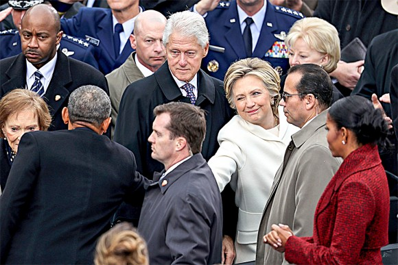 Former Democratic presidential nominee  Hillary Clinton shakes hands with President  Barack Obama as former president Bill Clinton looks on at the West Front of the U.S. Capitol on Jan. 20. (Joe Raedle/Getty Images)