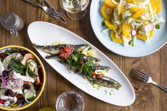 A plate of Sicilian sardines accompanied by a Greek salad. (Samira Bouaou/Epoch Times)