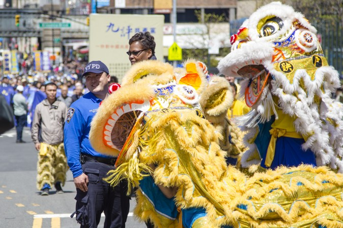 Police officers with a lion dance team at a parade in Flushing, New York, on April 23, 2017, to commemorate the 18th anniversary of the April 25th peaceful appeal of 10,000 Falun Gong practitioners in Beijing. (Samira Bouaou/The Epoch Times)