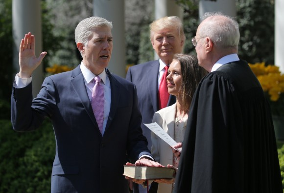 Judge Neil Gorsuch (L) is sworn in as an associate justice of the Supreme Court by Supreme Court Associate Justice Anthony Kennedy (R) , as U.S. President Donald J. Trump (C) watches with Louise Gorsuch in the Rose Garden of the White House in Washington on April 10, 2017. (REUTERS/Carlos Barria)
