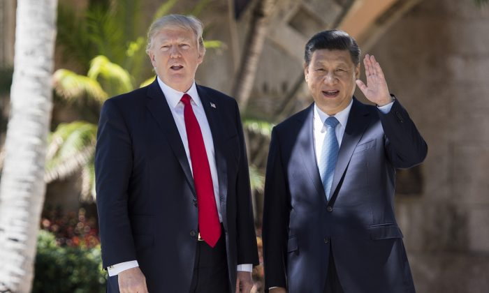 Chinese President Xi Jinping (R) waves to the press as he walks with US President Donald Trump at the Mar-a-Lago estate in West Palm Beach, Fla., on April 7, 2017. (Jim Watson/AFP/Getty Images)