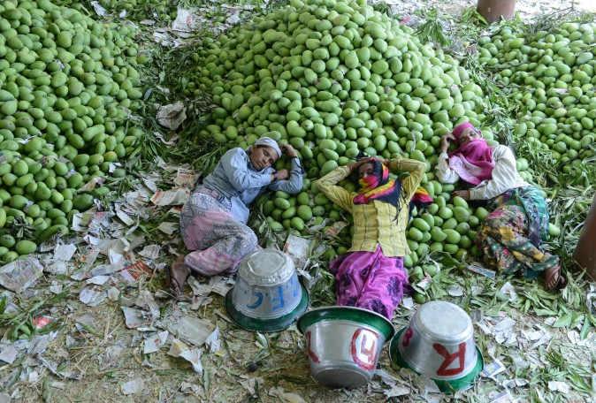 Indian workers rest after unloading mangoes at the Gaddiannaram Fruit Market on the outskirts of Hyderabad on April 12. India produces over 40 per cent of the world's mangoes, growing some 30 varieties commercially. (NOAH SEELAM/AFP/Getty Images)