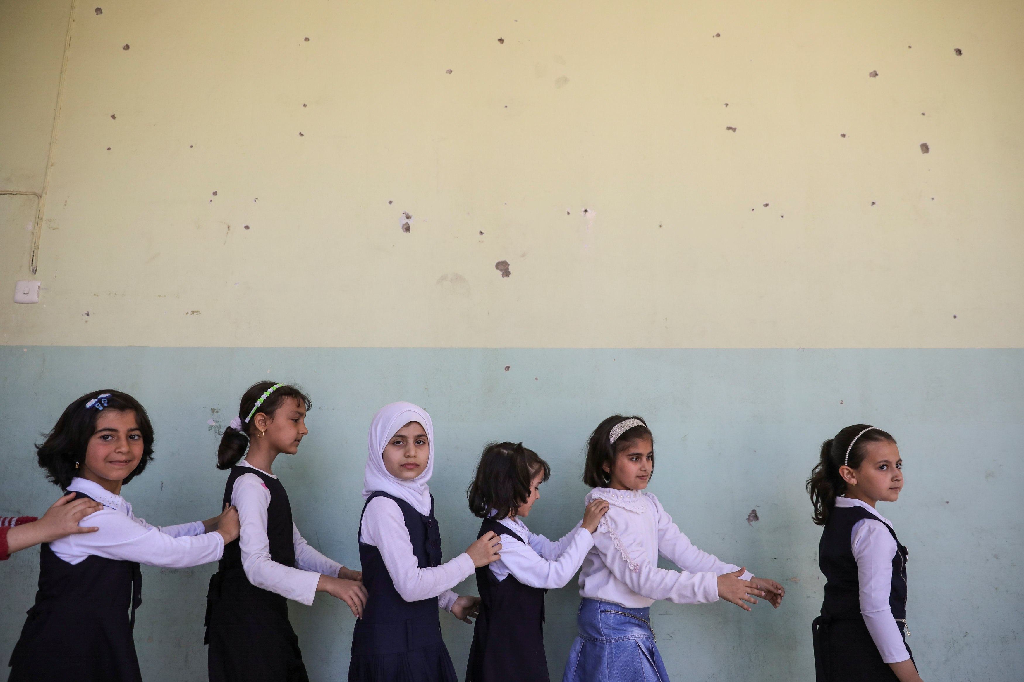 Pupils walk out from their classroom at an elementary school in eastern Mosul, Iraq on April 17, 2017. (REUTERS/Marko Djurica)