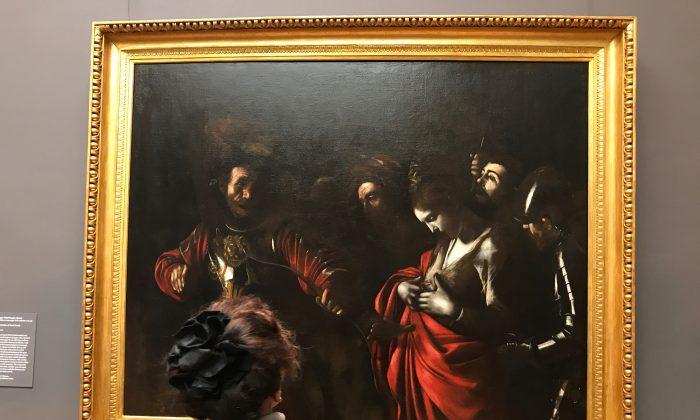 """A woman looks at """"The Martyrdom of Saint Ursula,"""" 1610, by Caravaggio (Michelangelo Merisi, Italian, 1571–1610). Oil on canvas, Intesa Sanpaolo Collection, Palazzo Zevallos Stigliano, Naples. (Milene Fernandez/The Epoch Times)"""
