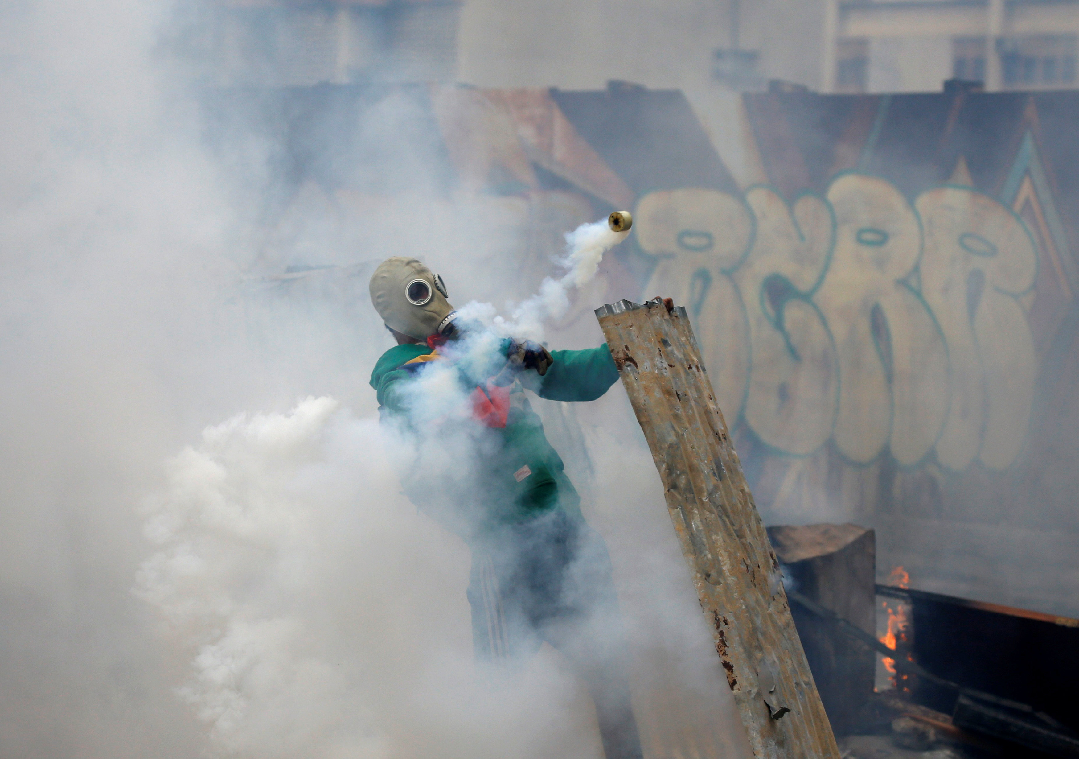 """An opposition demonstrator throws back a gas grenade while clashing with riot police during the so called """"mother of all marches"""" against Venezuela's President Nicolas Maduro in Caracas, Venezuela on April 19, 2017. (REUTERS/Carlos Garcia Rawlins)"""