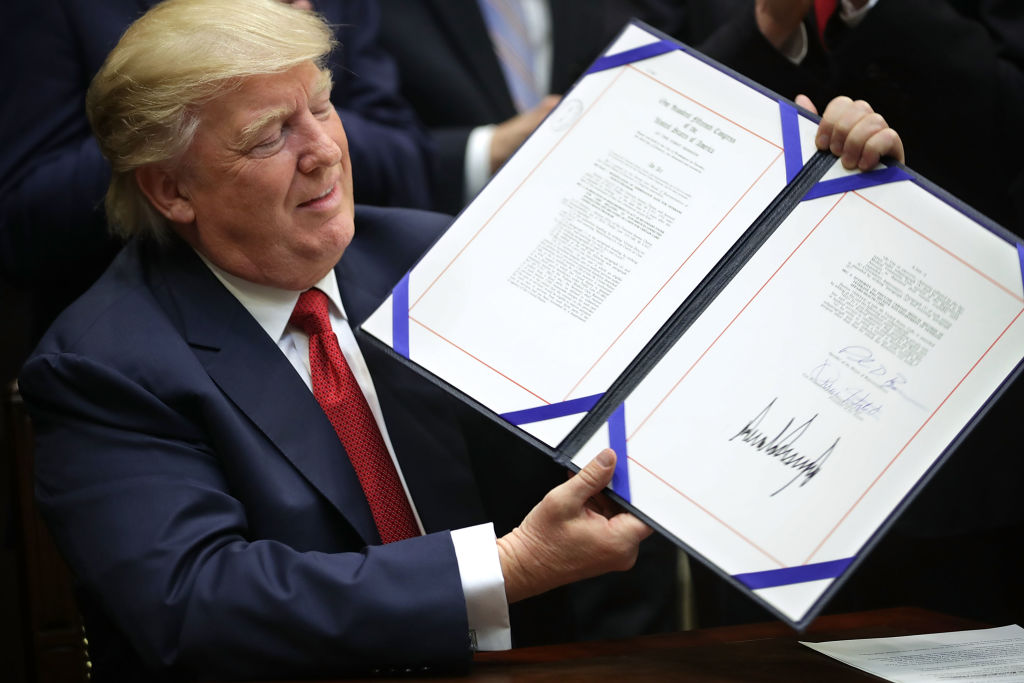 President Donald Trump holds up the Veterans Choice Program And Improvement Act after signing it in the Roosevelt Room at the White House in Washington on April 19, 2017. (Chip Somodevilla/Getty Images)