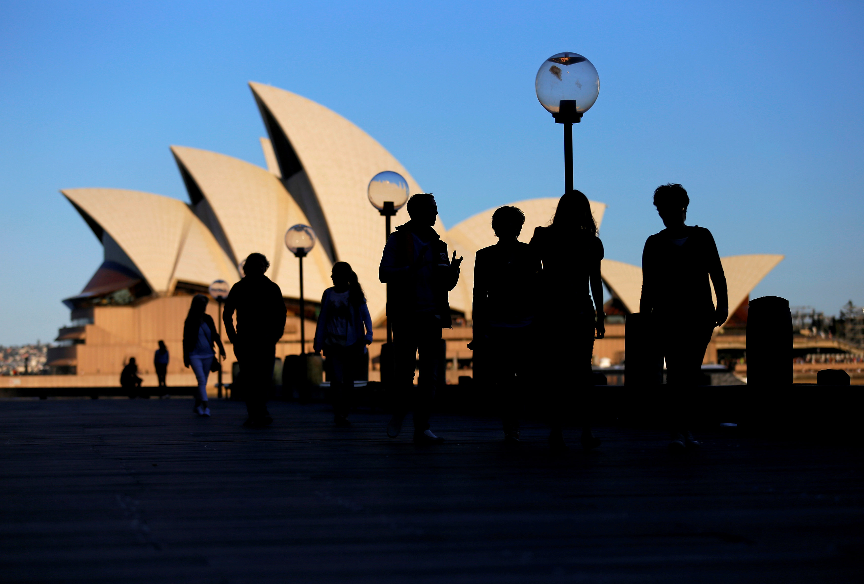 People walk in front of the Sydney Opera House, Australia on Nov. 2, 2016. (REUTERS/Steven Saphore)