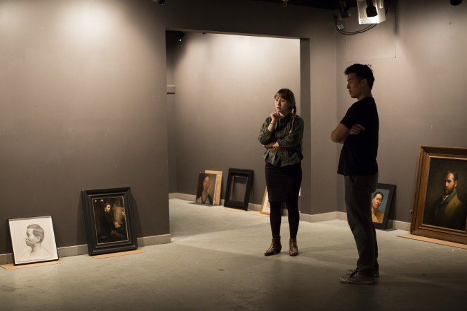 Artist and curator Colleen Barry and artist Samuel Hung prepare the Self Portrait exhibition at Eleventh Street Arts gallery in Long Island City, New York, on April 19, 2017. (Samira Bouaou/The Epoch Times)