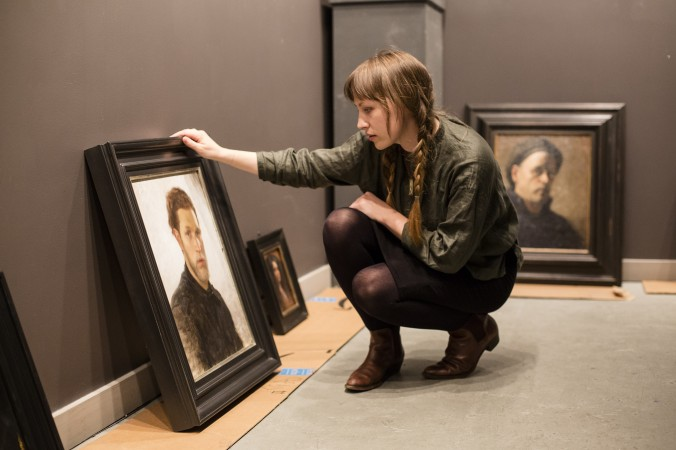 Colleen Barry, artist and curator, prepares the Self Portrait exhibition at Eleventh Street Arts gallery in Long Island City, New York, on April 19, 2017. (Samira Bouaou/The Epoch Times)