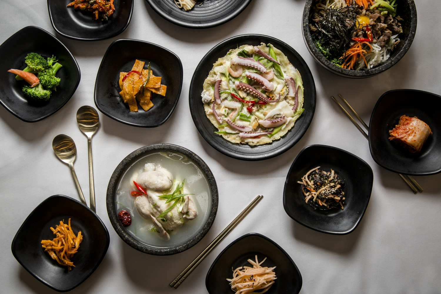 A colorful array of classic Korean dishes, alongside banchan, or side dishes, at missKOREA. (Samira Bouaou/The Epoch Times)