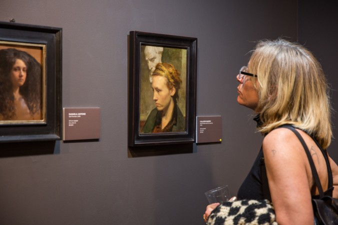 """A woman looks at self-portraits by (L) Daniela Astone and by Colleen Barry during the opening reception for """"Self Portrait"""" at Eleventh Street Arts in Long Island City, New York, on April 20, 2017. (Benjamin Chasteen/Epoch Times)"""