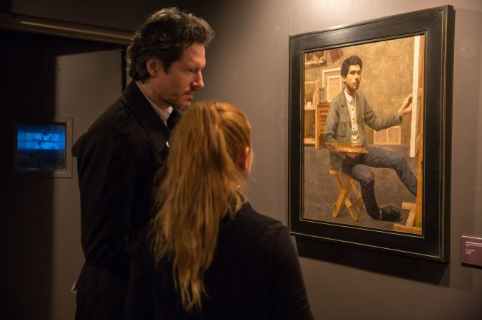 """Artists and guests look at a self-portrait by Rodrigo Mateo during the opening reception for """"Self Portrait"""" at the Eleventh Street Arts gallery in Long Island City, New York, on April 20, 2017. (Benjamin Chasteen/Epoch Times)"""