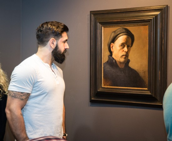 """A man looks at a self-portrait by Daniel Graves during the opening reception for """"Self Portrait"""" at the Eleventh Street Arts gallery in Long Island City, New York, on April 20, 2017. (Benjamin Chasteen/Epoch Times)"""