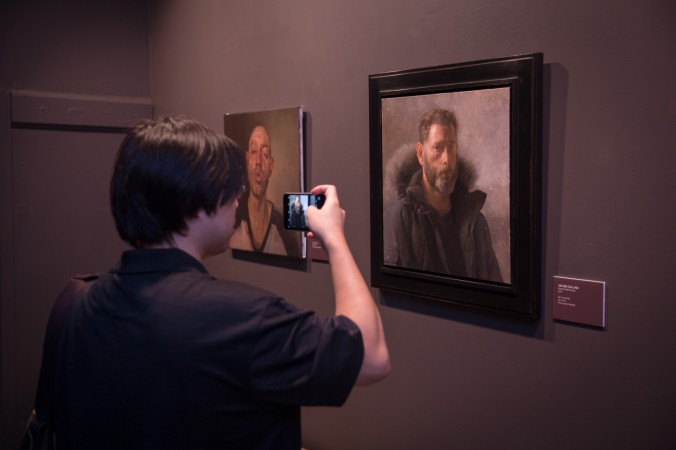 """A man takes a photo of a self-portrait by Jacob Collins during the opening reception for """"Self Portrait"""" at the Eleventh Street Arts gallery in Long Island City, New York, on April 20, 2017. (Benjamin Chasteen/Epoch Times)"""