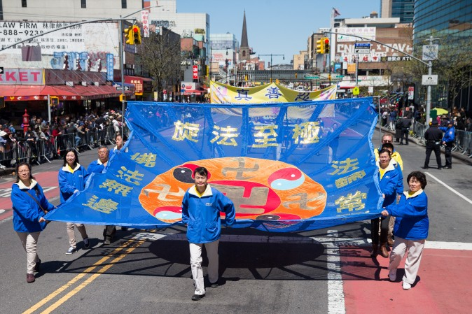 Falun Gong practitioners march in a parade in Flushing, New York, on April 23, 2017, to commemorate the 18th anniversary of the April 25th peaceful appeal of 10,000 Falun Gong practitioners in Beijing. (Larry Dye/The Epoch Times)