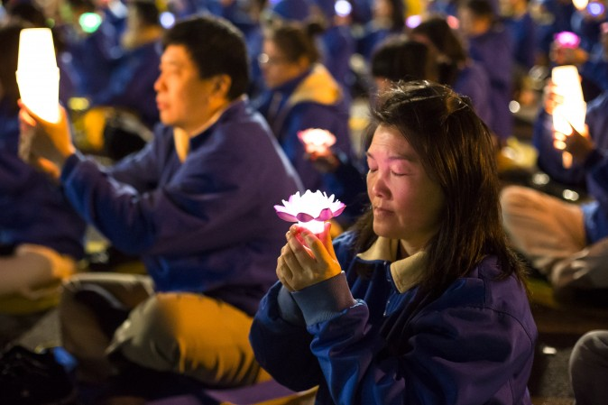 Falun Gong practitioners attend a candlelight vigil near the Chinese Consulate in New York on April 23, 2017. (Samira Bouaou/The Epoch Times)