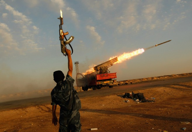 A rebel fighter celebrates as his comrades fire a rocket barrage toward the positions of troops loyal to Libyan ruler Moammar Gadhafi west of Ajdabiyah, Libya, on April 14, 2011.  (Chris Hondros/Getty Images)