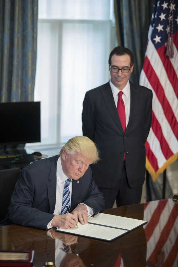 WASHINGTON, DC - APRIL 21: (AFP OUT) U.S. President Donald Trump (L), with Secretary of Treasury Steven Mnuchin (R), signs a financial services Executive Order during a ceremony in the US Treasury Department building on April 21, 2017 in Washington, DC. President Trump is making his first visit to the Treasury Department for a memorandum signing ceremony with Secretary Mnuchin. (Photo by Shawn Thew - Pool/Getty Images)